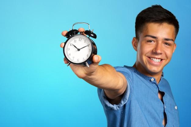 Jonge man met een wekker Premium Foto