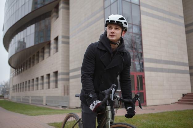 Jonge man met fietshelm tijdens het fietsen door de straten van de stad Premium Foto