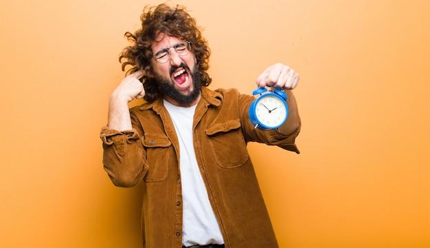 Jonge man met gek haar in beweging en een wekker Premium Foto