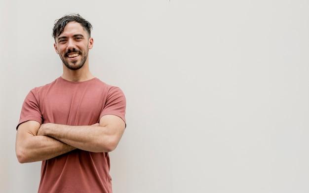 Jonge man met gekruiste armen en kopie-ruimte Gratis Foto