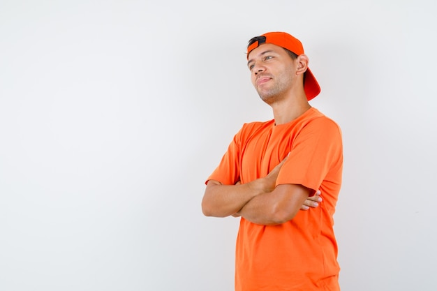 Jonge man met gekruiste armen in oranje t-shirt en pet en dromerig op zoek Gratis Foto