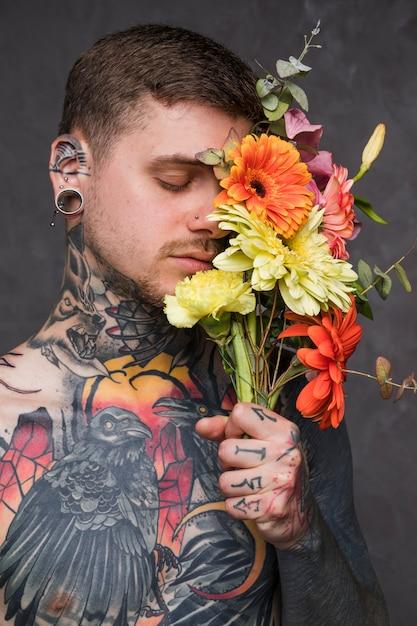 Jonge man met getatoeëerd op zijn lichaam bloem in de hand te houden Gratis Foto