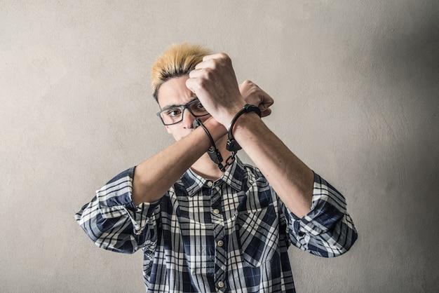 Jonge man met handboeien om de polsen Premium Foto