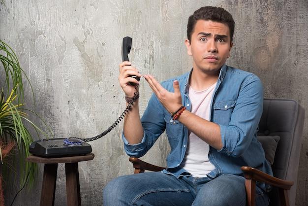 Jonge man met handset en zittend op een stoel. hoge kwaliteit foto Gratis Foto
