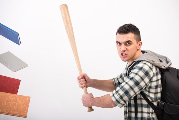 Jonge man met houten honkbalknuppel en boeken. Premium Foto