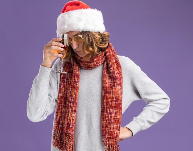Jonge man met kerst kerstmuts en gele bril met warme sjaal om zijn nek met glas champagne op zoek moe en verveeld depressief staande over paarse achtergrond Gratis Foto