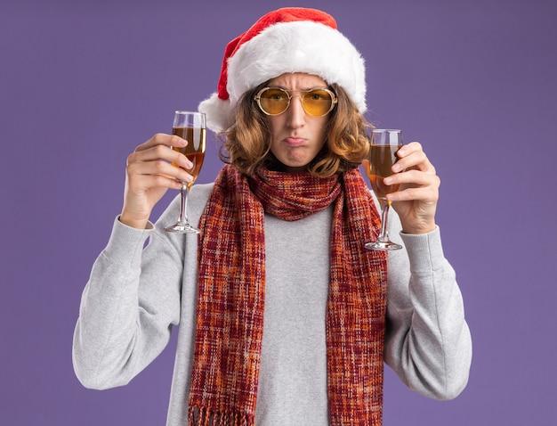 Jonge man met kerst kerstmuts en gele bril met warme sjaal om zijn nek met glazen champagne kijken camera verward makend wrange mond staande over paarse achtergrond Gratis Foto
