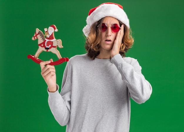 Jonge man met kerst kerstmuts en rode bril bedrijf kerst speelgoed camera verward en erg angstig kijken staan over groene achtergrond Gratis Foto