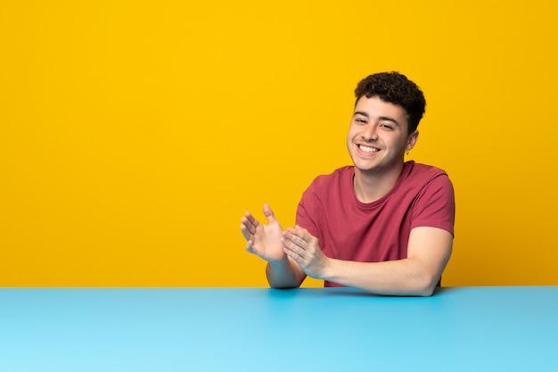 Jonge man met kleurrijke muur en tafel applaudisseren na presentatie in een conferentie Premium Foto