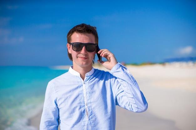 Jonge man met laptop en telefoon op de achtergrond van turquoise oceaan op tropisch strand Premium Foto