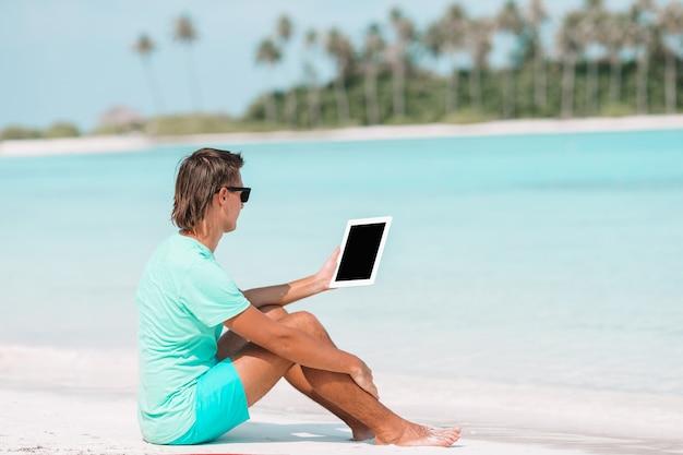 Jonge man met laptop op tropisch strand in de buurt van watervilla Premium Foto
