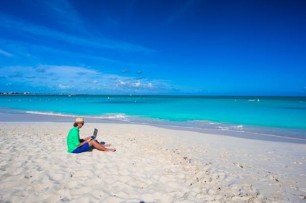 Jonge man met laptop op tropisch strand Premium Foto