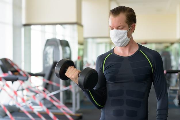 Jonge man met masker traint met halter op sportschool tijdens coronavirus covid-19 Premium Foto
