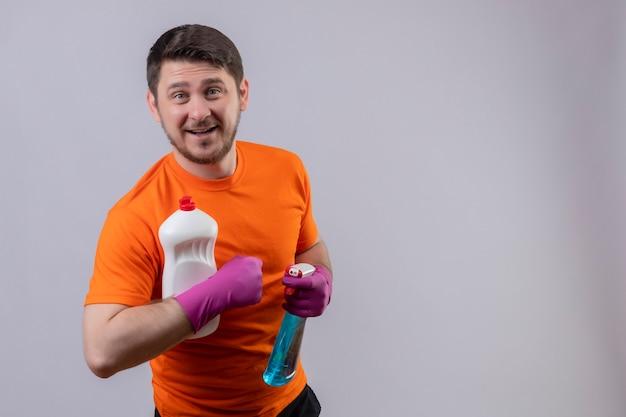 Jonge man met oranje t-shirt en rubberen handschoenen met flessen met schoonmaakproducten glimlachend vrolijk Gratis Foto