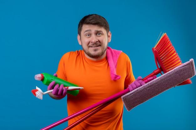 Jonge man met oranje t-shirt en rubberen handschoenen met reinigingsgereedschap Gratis Foto
