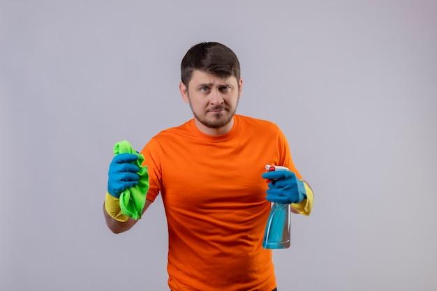 Jonge man met oranje t-shirt en rubberen handschoenen met reinigingsspray en deken ontevreden Gratis Foto