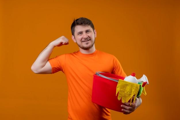 Jonge man met oranje t-shirt met emmer met schoonmaakgereedschap vuist omhoog glimlachend kijkend naar camera positief en blij verheugend zijn succes klaar om schoon te maken staande over oranje achtergrond Gratis Foto