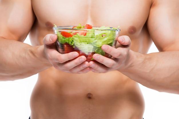 Jonge man met perfect lichaam houdt salade - geïsoleerd op een witte muur. Gratis Foto