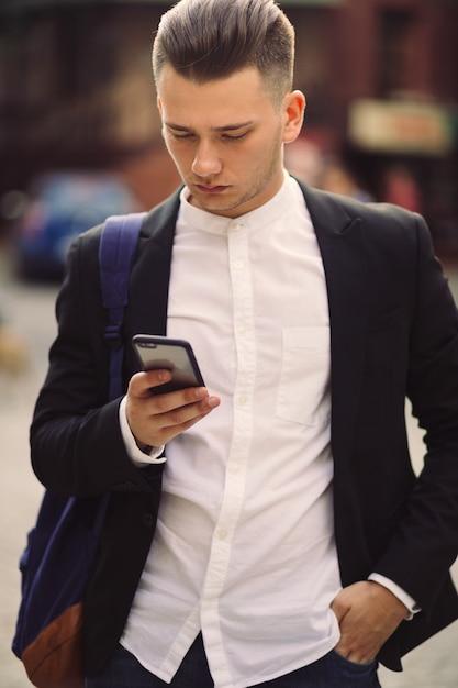Jonge man met rugzak met een telefoon Gratis Foto