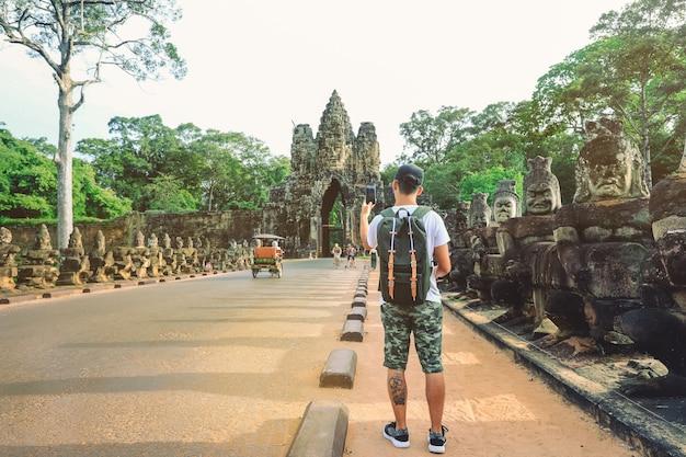 Jonge man met rugzak nemen foto van bayon tempel ingang angkor thom poort. siem reap, cambodja Premium Foto