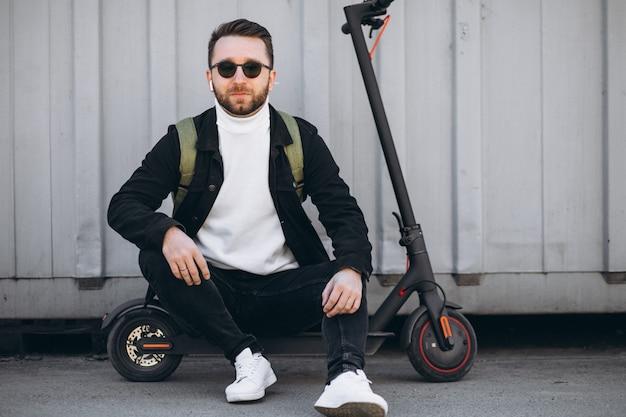 Jonge man met scooter, zittend op de grond Gratis Foto