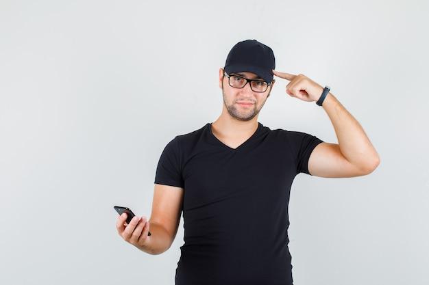 Jonge man met smartphone terwijl hij naar het hoofd wijst in zwart t-shirt Gratis Foto