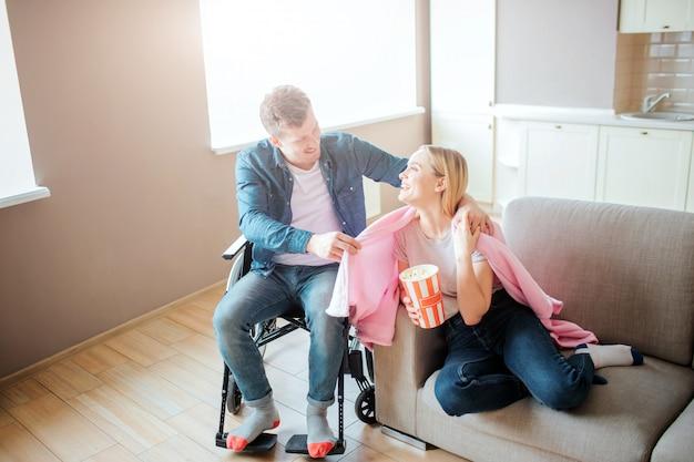 Jonge man met speciale behoeften zorgen voor vriendin. hij zit op een rolstoel en legt een deken op haar schouders. persoon met speciale behoeften. glimlachend naar elkaar. Premium Foto