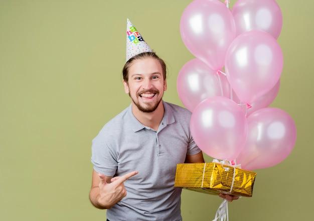 Jonge man met vakantie pet vieren verjaardagsfeestje bedrijf verjaardagscadeau en ballonnen blij en opgewonden glimlachend vrolijk staande over lichte muur Gratis Foto