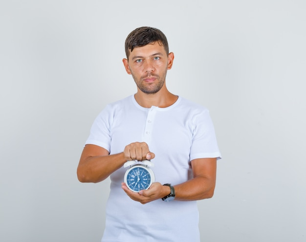 Jonge man met wekker in wit t-shirt en op zoek punctueel, vooraanzicht. Gratis Foto