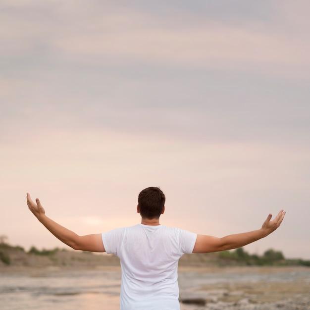 Jonge man met zijn armen in de lucht Gratis Foto