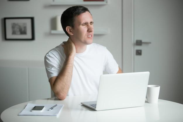 Jonge man met zijn handen aan zijn nek, zittend dichtbij bureau Gratis Foto