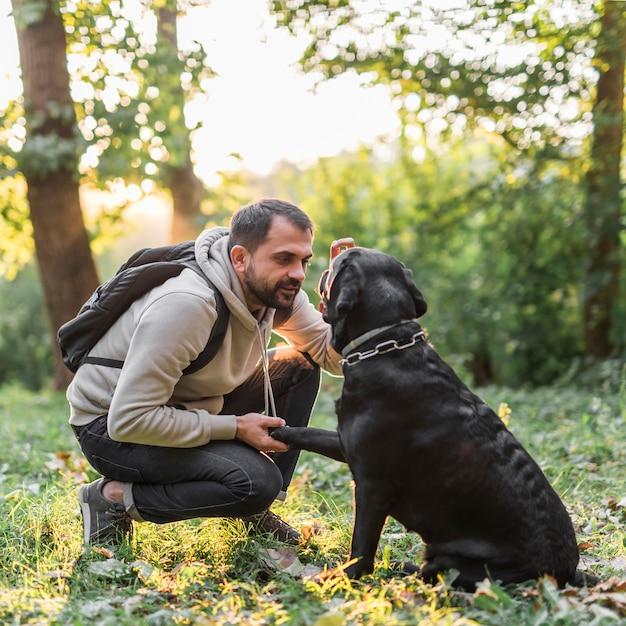 Jonge man met zijn hond in park Gratis Foto