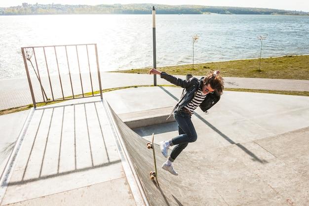 Jonge man met zijn skateboarden op de skatepark Gratis Foto