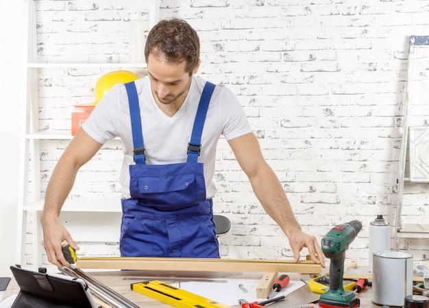 Jonge man meten houten plank Premium Foto