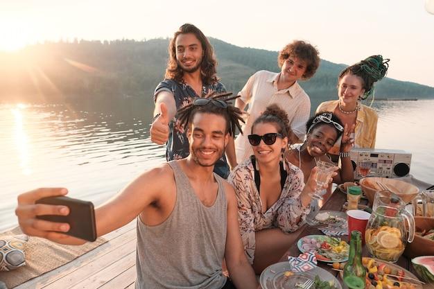Jonge man mobiele telefoon houden en selfie portret samen met zijn vrienden maken tijdens de lunch op een pier buiten Premium Foto