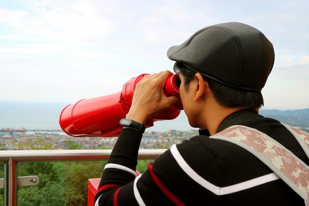 Jonge man observeren luchtfoto stadszicht met verrekijker vanaf het observatiedek Premium Foto