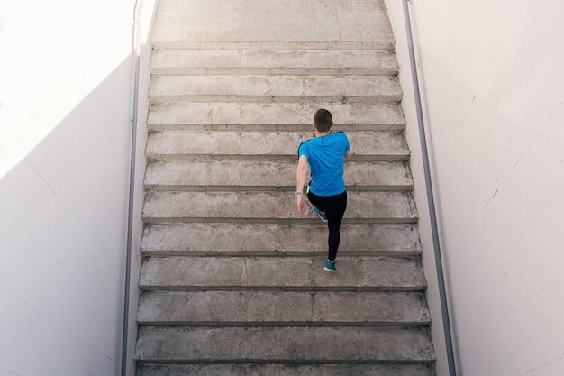 Jonge man oefenen intervaltraining op trappen Gratis Foto