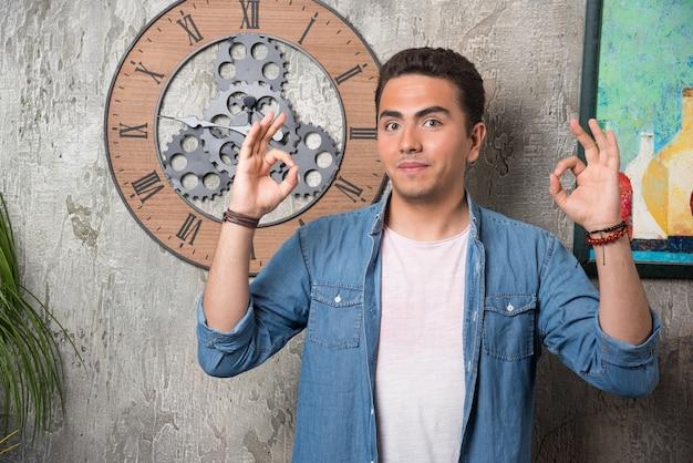 Jonge man ok gebaar tonen en poseren op marmeren achtergrond. hoge kwaliteit foto Gratis Foto