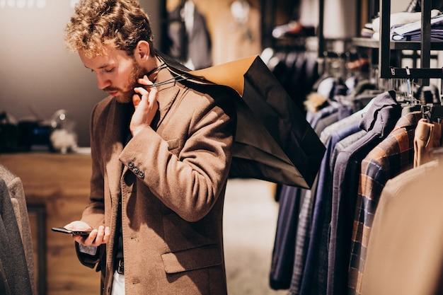 Jonge man op herenkleding winkel praten aan de telefoon Gratis Foto
