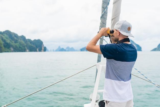 Jonge man op het jacht kijkt door een verrekijker. reizen en actief leven. Premium Foto