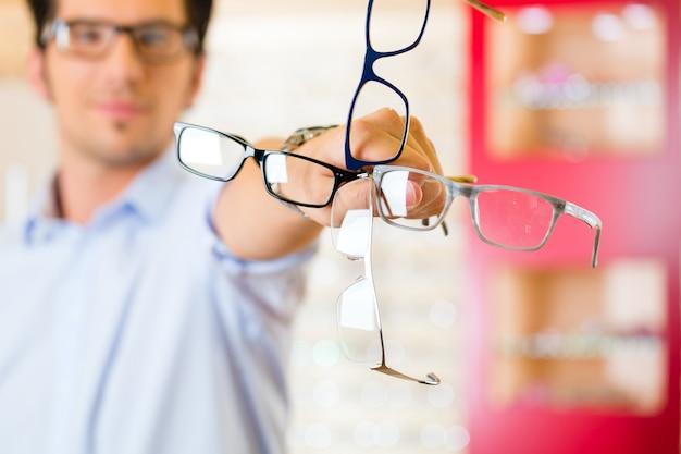 Jonge man op opticien met een bril Premium Foto