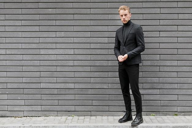 Jonge man op straat in de buurt van een grijze muur Gratis Foto