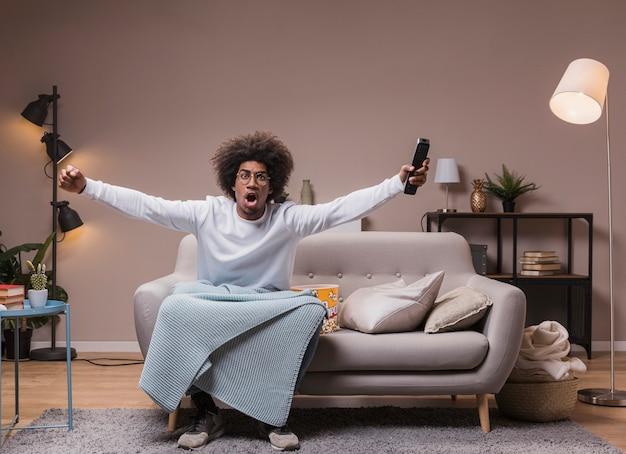 Jonge man opgewonden tijdens het kijken naar voetbal Gratis Foto