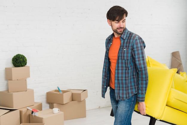 Jonge man opheffing van de gele bank in zijn nieuwe huis Gratis Foto