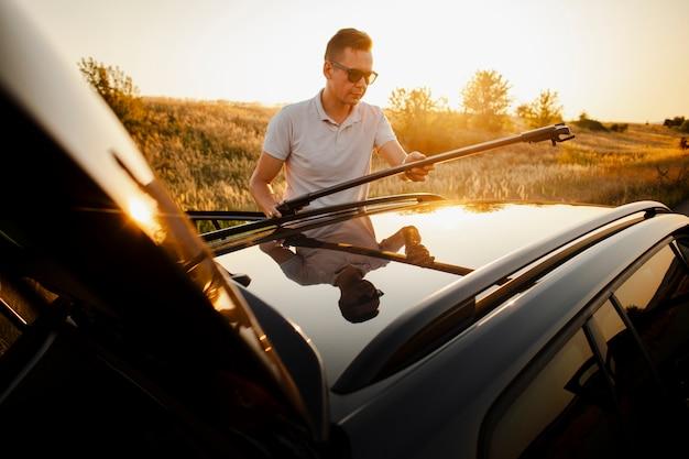 Jonge man opzetten van het autodak Gratis Foto