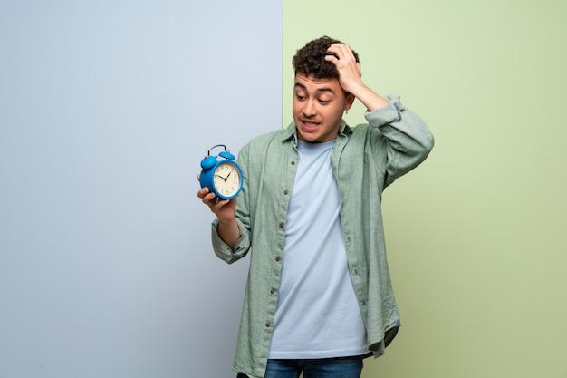 Jonge man over blauwe en groene muur onrustig omdat het laat is geworden en vintage wekker houdt Premium Foto