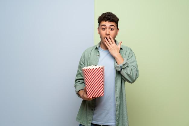 Jonge man over blauwe en groene muur verrast en het eten van popcorns Premium Foto