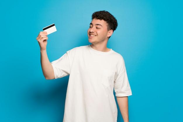 Jonge man over blauwe muur met een creditcard en denken Premium Foto