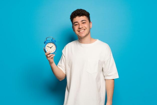 Jonge man over blauwe muur met vintage wekker Premium Foto