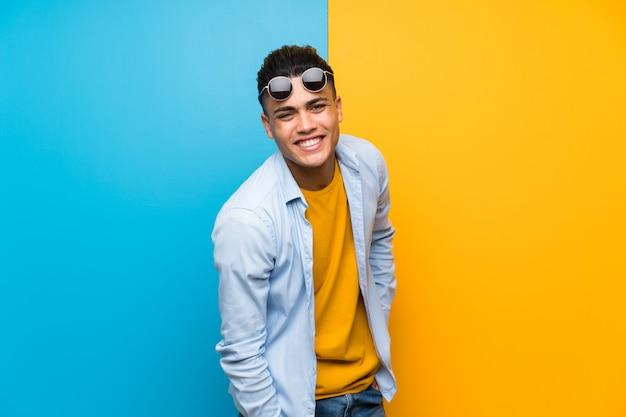Jonge man over geïsoleerde kleurrijke muur met zonnebril Premium Foto